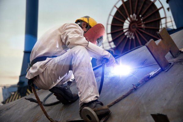 A welder at a shipyard